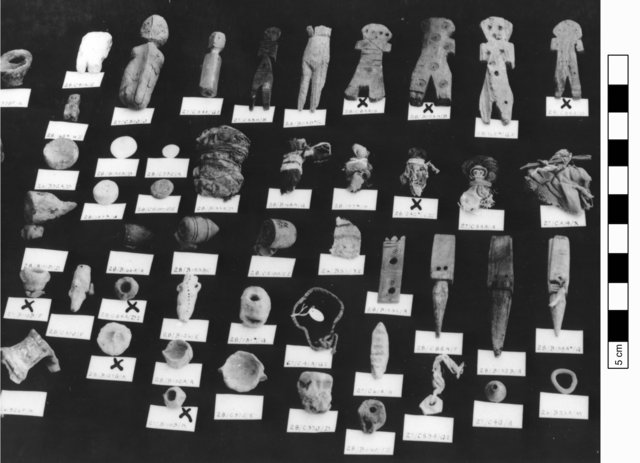 Fig. 2. Assortment of Karanis artifacts including textile dolls from expedition photograph (5.3681). In the second row, from right to left are:  KM 7513, KM 7512, Cairo Museum 54788, KM 7523, Km 7506. Sixth from right is KM 7508, excluded from this study; note the considerable size difference and lack of human characteristics.
