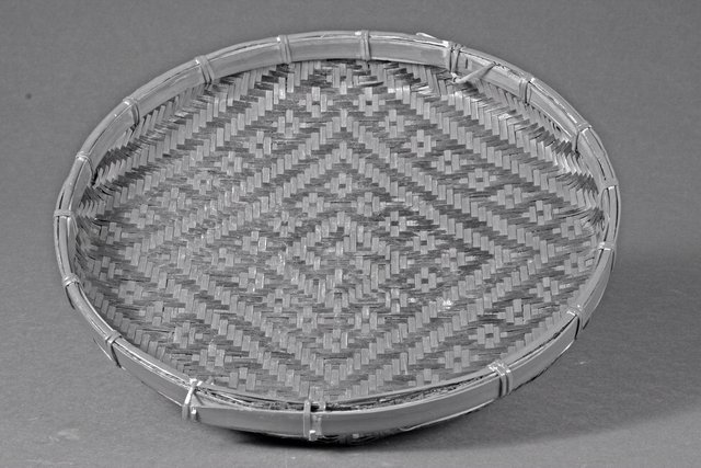 China. Flat basket, 20th century. Woven bamboo, 7 x 38.5 x 38.5 cm. Gift of Ellen and Richard Laing, 2006/2.36