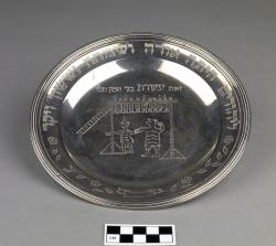 Plate; sterling silver, 19th century, with possibly 20th-century engraving added: scene of Mordechai and Haman surrounded by Hebrew text;