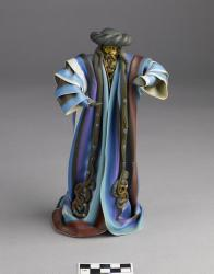 Figurine of a man in colorful robes; figure of brass and clay, robes of plastic, 9