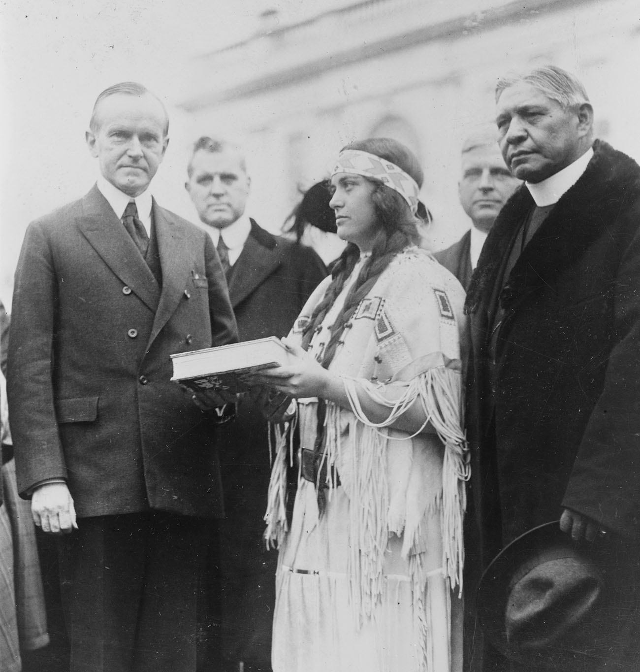 Figure 5.2. On December 13, 1923, Ruth Muskrat [Bronson] presented President Calvin Coolidge with a copy of The Red Man in the United States: An Intimate Study of the Social, Economic and Religious Life of the American Indian, by G. E. E. Lundquist (New York: George H. Doran Company). On June 2 of 1924, Congress would pass—and Coolidge would sign into law—the Indian Citizenship Act. Library of Congress, National Photo Company Collection. (c) Library of Congress, National Photo Company Collection (p. 25, no. 27839).