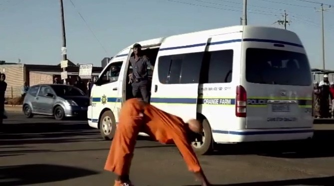 Figure 6: A Pantsula dancer blocks a police van, still from The African Cypher.