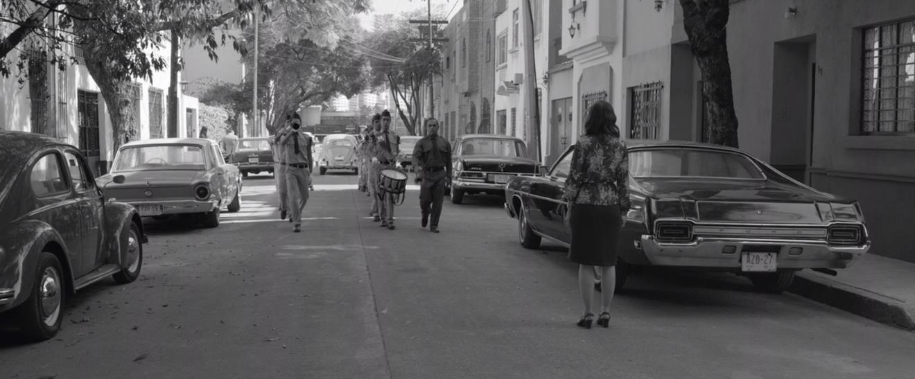 Figure 2: Lovesick Sofia (Marina de Tavira) watches as her husband (Fernando Gregiada) drives off in his Beetle,  while the shrillness of a drum and bugle corps only adds to her torment.