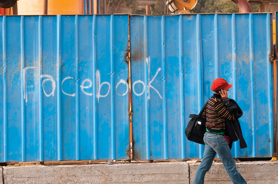 Figure 1.: Cairo, Egypt - February 25, 2011: An Egyptian woman walks past a wall with the word Facebook spray painted on it. Facebook was an important communications tool Egyptians used to organize the anti-government demonstrations that brought down the regime of Hosni Mubarak on February 11, 2011.