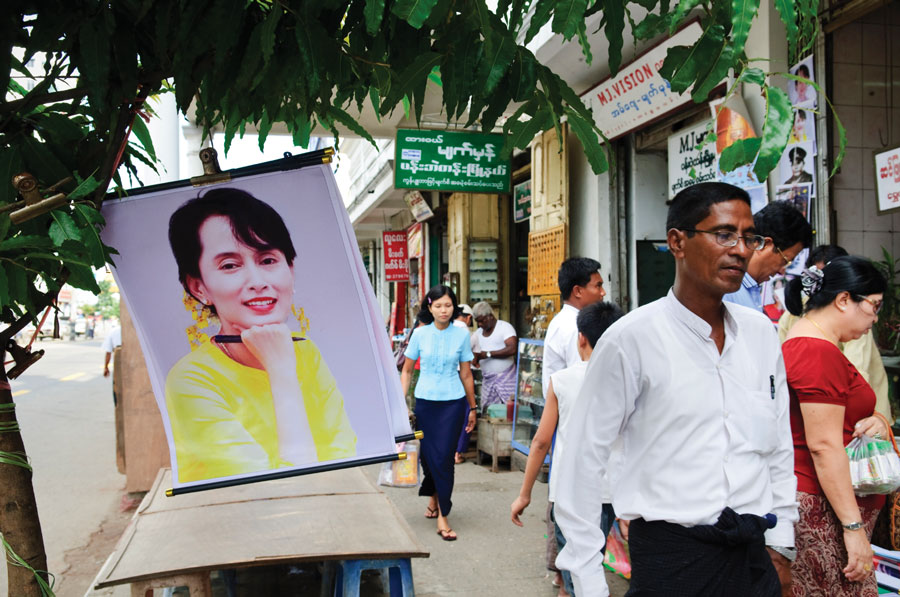 Figure 1.: Pedestrians walk past a poster-and-stationary shop where a poster of Aung San Suu Kyi is displayed for sale.