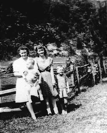 Figure 5. Helen Peake (left) and Catherine Thompson (right) pose ca.1942 near the Lincoln Cabin with Helen's two sons—James Edward Peake and Howard Peake—both born at the Knob Creek Farm. Photo courtesy Jack Beam.