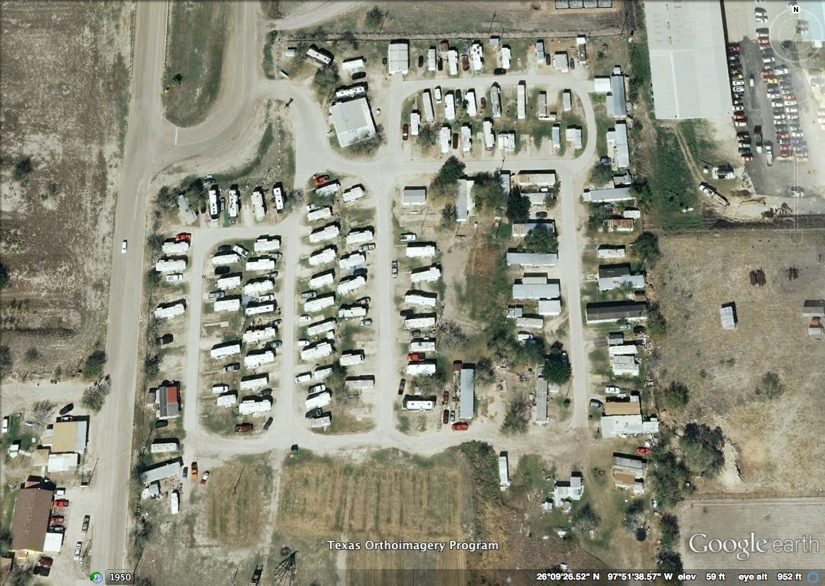 Figure 1: Aerial view of a colonia near Mercedes, Texas in the Lower Rio Grande Valley. This aerial depicts the layout of a typical colonia, showing a mixture of housing types: second-hand mobile homes, repurposed airstreams, and makeshift shacks. To get a sense of the small sizes of the homes and lots, consider the sizes of the homes in relation to the cars parked beside them. Note that this colonia has only partially paved roads.