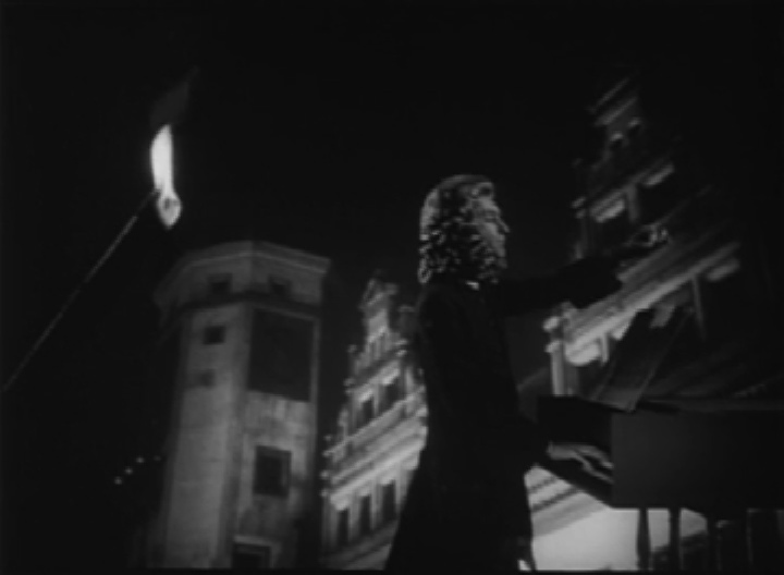 Figure 1.: Gustav Leonhardt as J.S. Bach, shown conducting with rear projection of the St. Thomas School (shot 57).