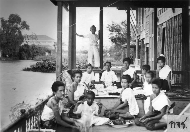 "Figure 5. Bunnag sisters and children sharing a meal on the veranda of the king's residence, Ruen Ton (""Wooden House""), at Dusit Palace."