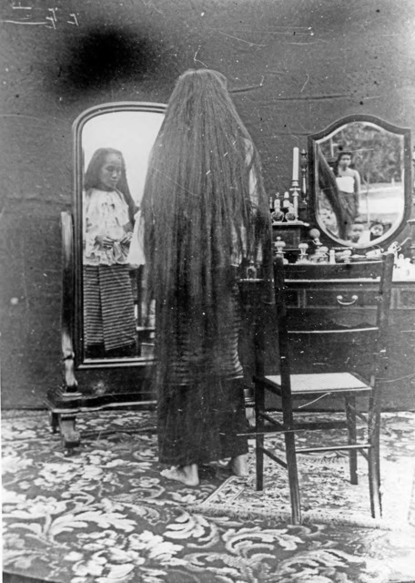 Figure 23. The Princess' hair, completely loose, reaches nearly to her ankles. Note that Erb and her camera are visible in the reflection of the tabletop mirror (right).