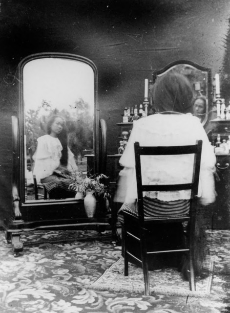 Figure 25. The seated Princess, hair obscured, her face doubly reflected in both mirrors.