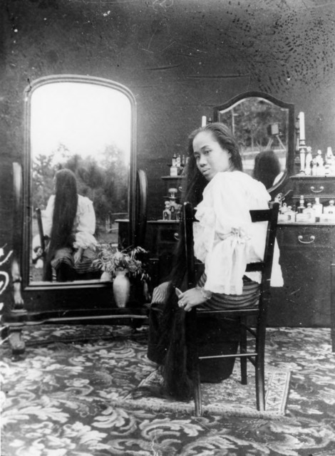 Figure 27. Princess Dara Rasami, her hair loose, looks back at the camera. Note the reflection in the mirror on the left, which provides a view of her long hair from another angle.