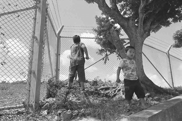 "Mao Ishikawa, ""Catching cicadas along the Futenma Air Base fence line. August 2009. Ginowan City, Okinawa"", from the Fences series, ©Mao Ishikawa."