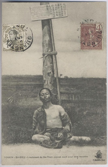 "Figure 2: series number 3332 (vertical variation), BA-BIEU - lieutenant du Dê-Tham exposé mort pour être reconnu, (""BA-BIEU - lieutenant of  Dê-Tham, exposed dead for recognition""), image attributable to Captain Péri, postcard published by Pierre Dieulefils, Hanoi, ca. 1909, sent within northern Vietnam to a colonial military address, postmarked  January (day and year illegible)."