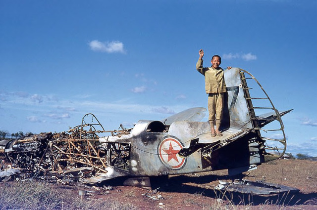 Figure 1. John Rich, A Korean Boy on the remains of a Russian built North Korean Yak fighter plane, c. 1950. Kodachrome.