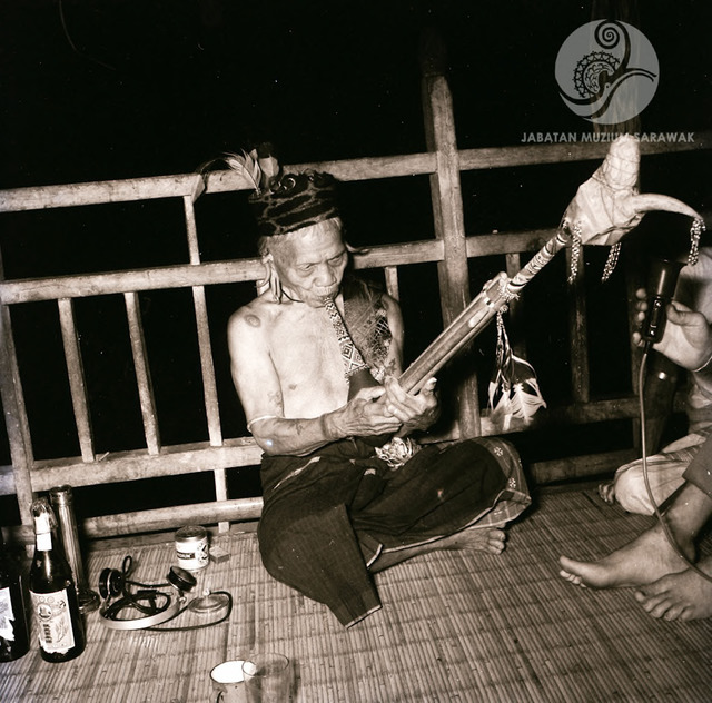 Figure 5: Datuk Moyang Jau playing the Kelunaye on the verandah of Long Jegan, while a researcher is recording the music with a microphone, 1956. Photograph from the archive of the Sarawak Museum.
