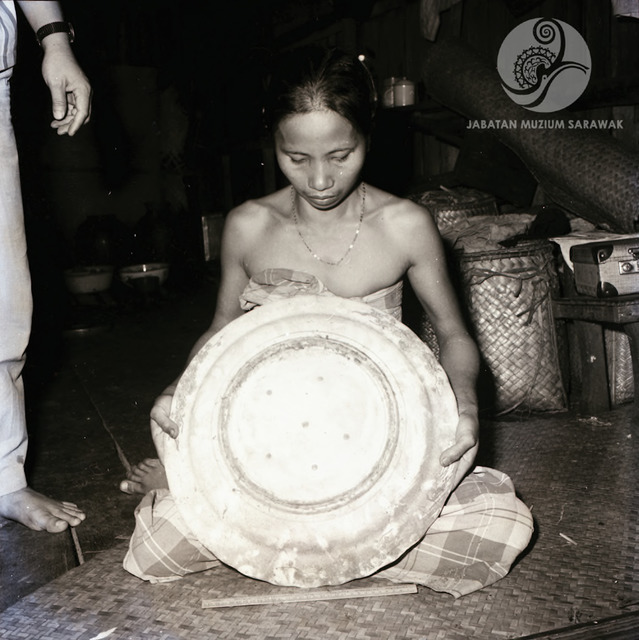 Figure 6: Woman presenting her heritage ceramics to museum staff, location unknown, 1968. Photograph from the archive of the Sarawak Museum.