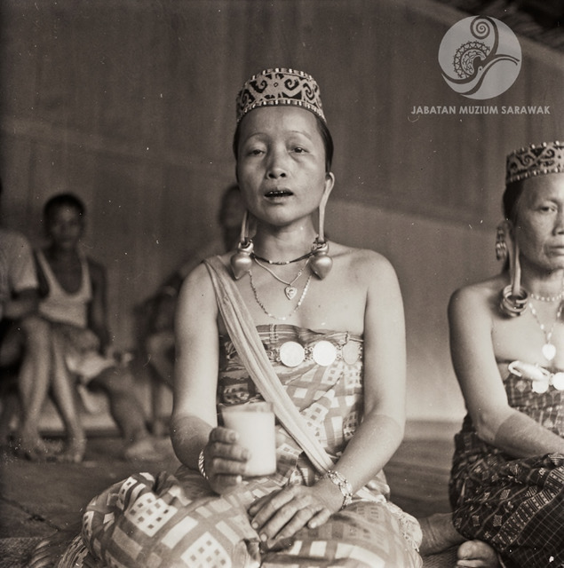 Figure 9: Lalang Saging and Ubong Lian, singing a Kenyah welcome song, and holding a glass of rice wine the visitor is given at the end of the song, 1956. Photograph from the archive of the Sarawak Museum.