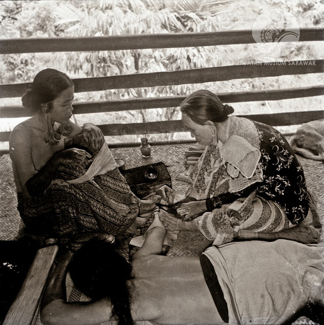 Figure 17: Two women tattooing a third at Long Jegan longhouse. This photograph, taken in 1956, is part of a series on tattooing exhibited in the ethnographic section of the Sarawak Museum. Photograph from the archive of the Sarawak Museum.