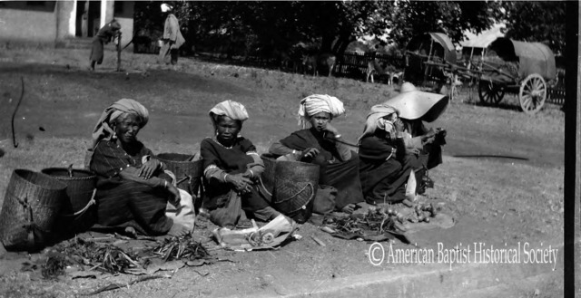 Four Pa-Oh women and one man (under the hat) in the 5-day bazaar at Taunggyi, Southern Shan State. Note the vegetables for sale, on dirty mats on the ground. See, also, the bracelets and heavy earrings, for these people carry all of their wealth with them. March 11, 1922.