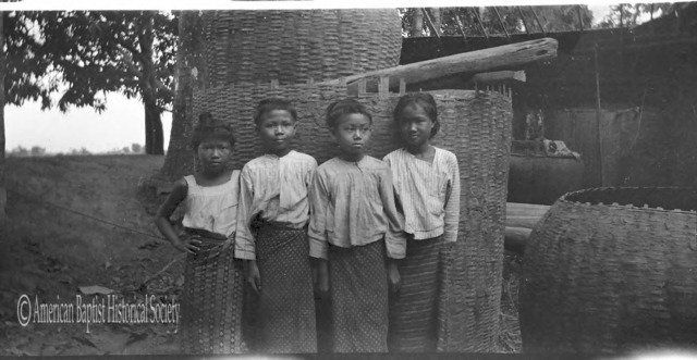 Four Burmese girls at Thabaung [Irrawaddy Division]. The large baskets are filled with [rice] paddy. April 2, 1923.