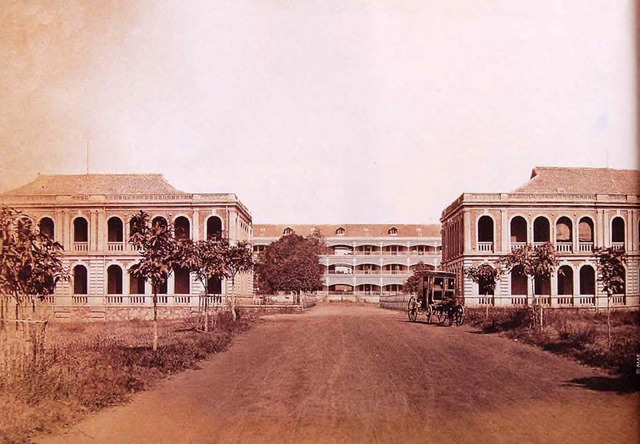 "Fig. 4. Colonial Navy Grounds, 1882. The road in front with the building at the center is Ðinh Tiên Hoàng Street. Parts of the buildings on the left (which belonged to the College of Pharmacy) and right still exist. The resolution of the image is very high, as though by ""zooming"" one would see that, in the middle building, a sailor in white is staring at the photographer, while on the left a gardener brings water under the tree."