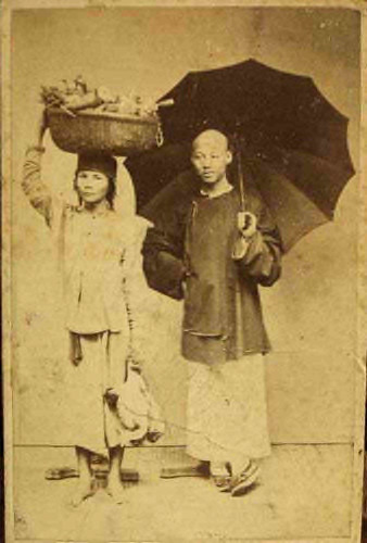 Fig. 11. Pun Lun, Studio Photograph of people from Saigon, 1880, (a market woman carrying goods on her head and probably a Chinese merchant with an umbrella).