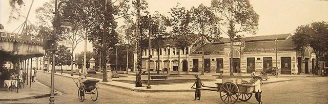 "Fig. 30. Ludovic Crespin – Saigon at the start of the 1920s: Place de l'hôtel de ville, boulevard Bonnard, boulevard Charner. Municipal Hotel Plaza, corner of Bonnard (now Lệ Lợi) and Charner (now Nguyễn Huệ) Avenues. Right in the middle of Lệ Lợi is a public park with a statue of Francis Garnier facing the Municipal Theater. On the right is the shop ""Auto-Hall,"" which sold all kinds of automobiles. On the left is the establishment Pancrazi, which was open until the wee hours of the night. The cart-pullers on the right are staring in the direction of the photographer (Crespin).."
