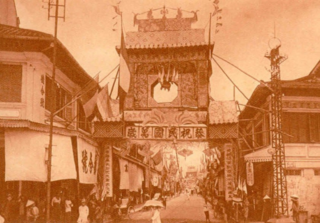 "Fig. 32. Fernand Nadal, from Album Nadal, 1926: Canton Street (now Triệu Quang Phục). This image also appeared as a postcard. Probably it is the national holiday commemorating the establishment of the Republic of China on October 10, 1911. At the head and end of the street are congratulatory gates with the Chinese inscription, ""Ten thousand years to the Republic.""  On the left side of the gate hang the tricolor flags of France."