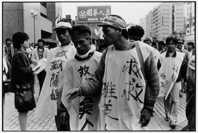 "Guan Xiao-rong, Indigenous demonstrators, in front of the headquarters of the Taiwan Power Company, wear clothing that reads ""Help Yami people"", © Guan Xiao-rong, courtesy the artist."